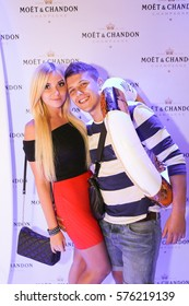 Odessa, Ukraine July 11, 2015: Beautiful glamorous men, women, boys and girls posing for the camera on the background wall of champagne brand Moet during elite Luxury partying in a nightclub