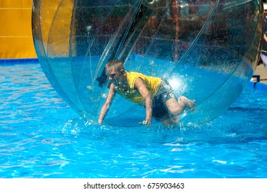 Odessa, Ukraine - July 11, 2017. Little children in an inflatable balloon, having fun on the water. The ball in the water - fascinating summer attractions for children. Water zorbing.