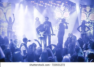 Odessa, Ukraine July 12, 2014: Ibiza night club. Artist The Party Makers performs clud show from stage during concert at nightclub with lights show. Artist on club stage during night party.