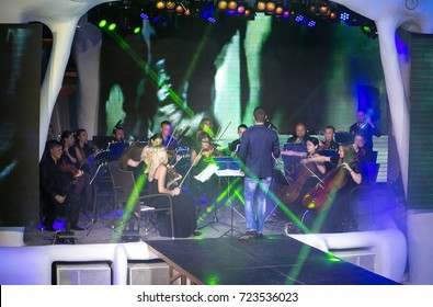 Odessa, Ukraine July 12, 2015: Ibiza night club. Artist performs clubs show with orchestra from stage during concert at nightclub with lights show. Artist on club stage during night party.