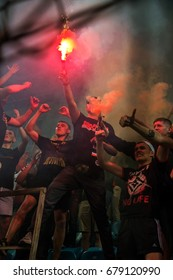 ODESSA, UKRAINE - July 15, 2017: Super Cup. Shakhtar - DYNAMO (Kiev). Fanatical fans in stands during game of eternal rivals. Fans on stands joy, light fire and waving flag. Fiery show at stadium