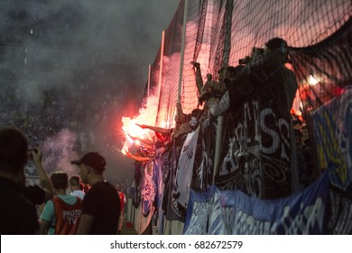 Odessa, Ukraine July 15, 2017: Shakhtar - Dynamo (Kiev). Footbal Ultras on stadium. Fanatical fans in stands during game of eternal rivals. Fans on stands joy, light fire and waving flag. Fiery show