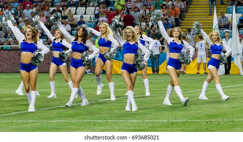 ODESSA, UKRAINE - July 15, 2017: Performance of beautiful young girls of cheerleader team during opening of football championship. Team performance cheerleader on grass field of stadium