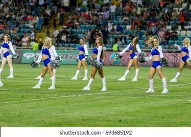 ODESSA, UKRAINE - July 15, 2017: Performance of beautiful young girls of cheerleader team during opening of football championship. Team performance cheerleader on grass field of stadium