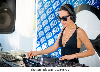 Odessa, Ukraine July 18, 2015: Ibiza beach club. dj girl in bikini playing good music at summer pool party. Day lounge party at luxury summer club. Ibiza dj at work