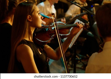 ODESSA, UKRAINE - July 19, 2018: Symphony Orchestra on stage. Musical show on stage of theater. Musicians of symphony orchestra, musical instruments. Jazz band on stage. Selective focus