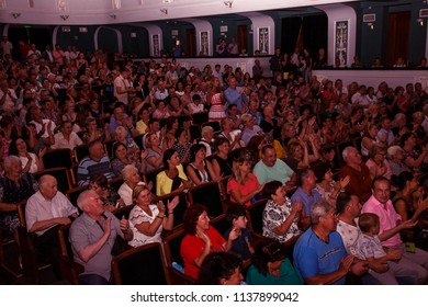 ODESSA, UKRAINE - July 19, 2018: Spectators in auditorium of concert hall emotionally meet their favorite performers. audience in theater hall. Viewers like performance on stage of theater