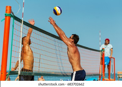 ODESSA, UKRAINE - July 22, 2017: beach volleyball. Holidaymakers on beach are young sports men and women playing beach volleyball in sea. volleyball court with players on sand. Selective focus
