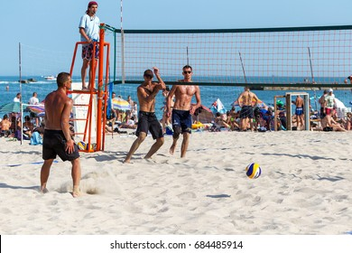 ODESSA, UKRAINE - July 22, 2017: beach volleyball. Holidaymakers on beach are young sports men and women playing beach volleyball near the sea. volleyball court with players on sand.