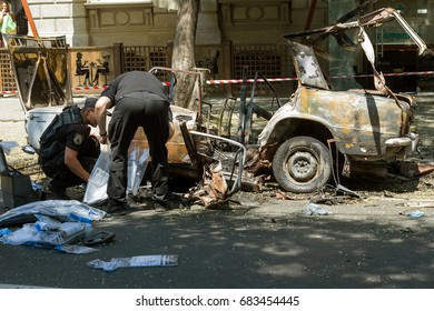 ODESSA, UKRAINE - July 24, 2017: Police, explosives technicians, forensics inspect  car burned from an explosive as result of terrorist act. Blown up, burned car. police work at crime scene. Terror