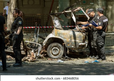ODESSA, UKRAINE - July 24, 2017: Police, explosives technicians, forensics inspect  car burned from an explosive as result of terrorism. Blown up burned car. police work at crime scene. Terror in city