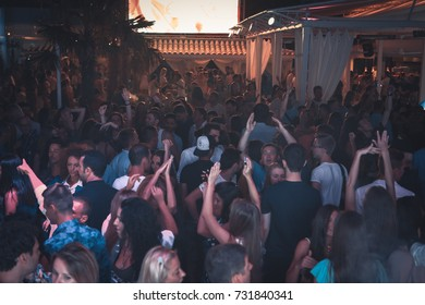 Odessa, Ukraine July 25, 2015: Ibiza Night club dj party people enjoy of music dancing sound with colorful light, smoke machine, lights show and dance show. Hands up in the earth.