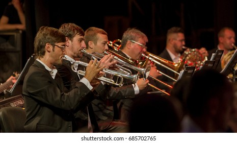 "ODESSA, UKRAINE - July 26, 2017: Orchestra on stage. Musical show ""Battle of the Orchestras."" Musicians of symphonic variety orchestra, musical instruments. Jazz Orchestra on stage. Selective focus"