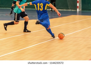 Odessa, Ukraine - July 28 2018: Unidentified players of local team playing in mini-football tournament in futsal on parquet floor. Вright moment of sport game in football in closed hall, mini football