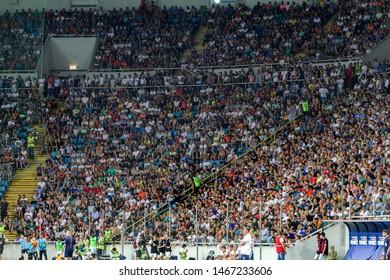 ODESSA UKRAINE - July 28, 2019: spectators at stadium. Crowds of fans in stands of football stadium during match Shakhtar (Donetsk) -Dynamo (Kiev). Grandstand with fans. Stands with football fans