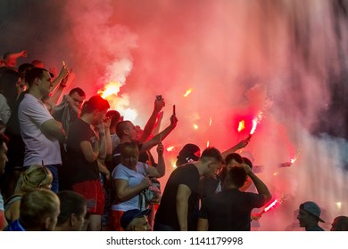 ODESSA, UKRAINE -July2,2018: Fanatical fans in stands during game of eternal rivals. Fans on racks are happy, glow with fire and waving flag. Fiery show at stadium. Fans of hooligan light fiery flashe