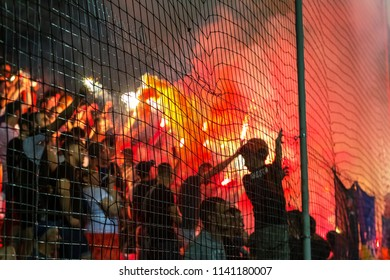 ODESSA, UKRAINE -July2,2018: Unsharp background. Fanatical fans in stands during game of eternal rivals. Fans on racks are happy, glow with fire and waving flag. Fans of hooligan light fiery flashe