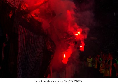 ODESSA, UKRAINE -July28,2019: Fanatical fans in stand during game of eternal rivals. Fans on racks are happy, glow with fire and waving flag. Fiery show at stadium. Fan of hooligan light fiery flashe