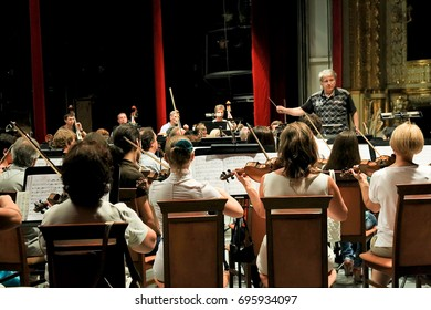 """Odessa, Ukraine -  June 08, 2013: Symphonic orchestra of conductor performs on stage playing instruments music. """"International Festival of Arts"""" Odessa National Theater of Opera and Ballet"""