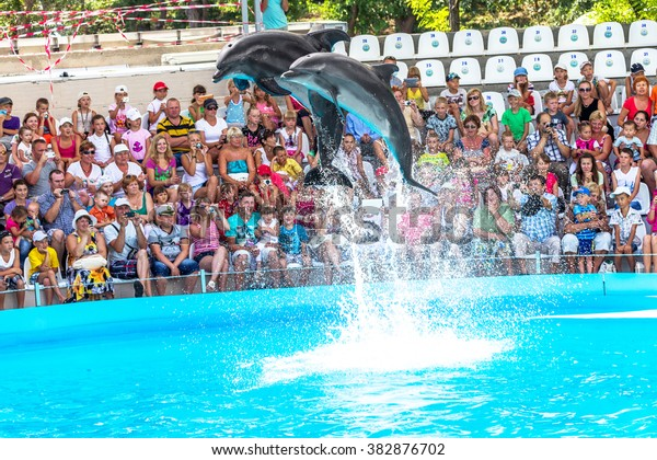 ODESSA, UKRAINE - JUNE 10, 2013: Dolphins on creative entertaining show at the dolphinarium with the full house of visitors show amazing tricks. Spectators happily delighted