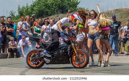 ODESSA, UKRAINE - June 10, 2018: Auto show. Beautiful girls present to spectators, the public with legendary cars, motorcycles during drifting with smoke on cars, motorcycle shows