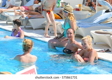 Odessa, Ukraine June 13, 2015: Pool party at summer club during holidays time. Enjoying pool party with friends. Group of beautiful young people looking happy into the swimming pool together.