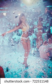 Odessa, Ukraine June 13, 2015: Ibiza night party festival crowd of people silhouettes hands up with confetti. Nightclub party. Colorful lights during dj party at concert in night club.
