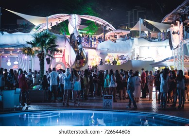 Odessa, Ukraine June 20, 2015: Ibiza Night club dj party people enjoy of music dancing sound with colorful light with Smoke Machine and lights show. Hands up in the earth.