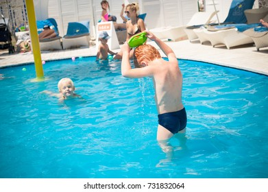 Odessa, Ukraine June 26, 2014: Parent and baby in swimming pool. Parent and child swim in a tropical resort. Summer outdoor activity for family with kids. Vacation and traveling with young children.