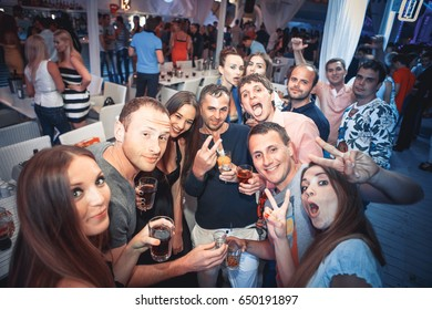 Odessa, Ukraine June 28, 2014: Ibiza night club. People smiling and posing on cam during concert in night club party. Man and woman have fun at club. Boy and girl at night club party