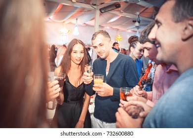 Odessa, Ukraine June 28, 2014: Ibiza club. People smiling and posing on cam during concert in night club party. Man and woman have fun at club. Boy and girl at night club party