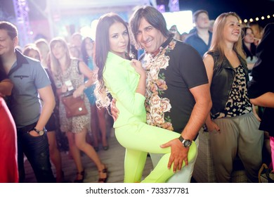 Odessa, Ukraine June 29, 2014: Ibiza club. People smiling and posing on cam during concert in night club party. Man and woman have fun at club. Boy and girl at night club party