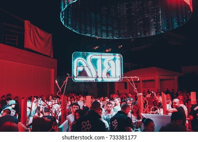 Odessa, Ukraine June 29, 2014: Ibiza Night club dj party people enjoy of music dancing sound with colorful light, smoke machine, lights show. Hands up in the earth.