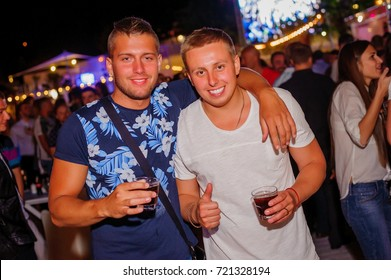 Odessa, Ukraine June 5, 2015: Ibiza night club. People smiling and posing on cam during concert in night club party. Man and woman have fun at club. Boy and girl at night club party