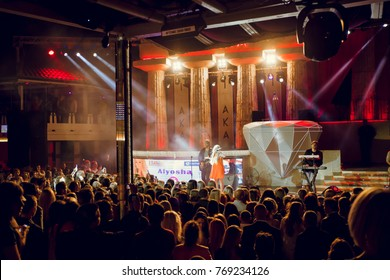 Odessa, Ukraine June 5, 2015: Night club dj party people enjoy of music dancing sound with colorful light, smoke machine, lights show and dance show. Hands up in the earth.