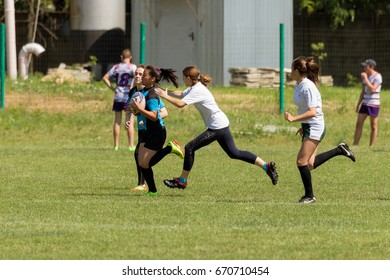 ODESSA, UKRAINE - June 6, 2017: brutal rugby fight between women's teams. Girls Players assiduously grasp opponents in fight for ball in rugby cup. Rugby women seize each other in dispute over ball