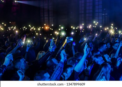 ODESSA, UKRAINE - March 23, 2019: viewers in auditorium of concert hall emotionally meet their favorite performers. Audience in theater hall. Viewers like performance on stage