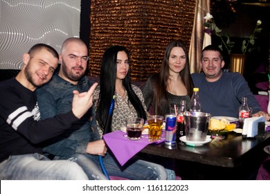 Odessa, Ukraine March 4, 2016: People smiling and posing on cam during concert in night club party. Man and woman have fun at club. Boy and girl at night club party