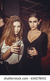 Odessa, Ukraine March 7, 2017: beautiful girl drink alcohol, smiling and posing on cam during concert in night club party. woman have fun at club