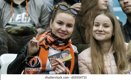 ODESSA, UKRAINE - May 13,2017: Active fans in stands of stadium with attributes of their favorite team during game of football teams of Paris-Match league. Fans on stadium celebrate victory of team FC