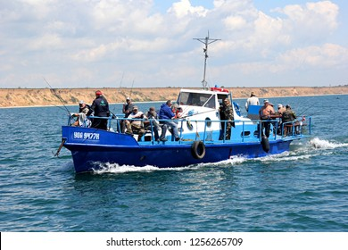 Odessa, Ukraine - may 15, 2016: A blue fishing ship with sea fisherman goes to sea to catch bullhead goby fish. Beautiful seafront in the background. Black sea