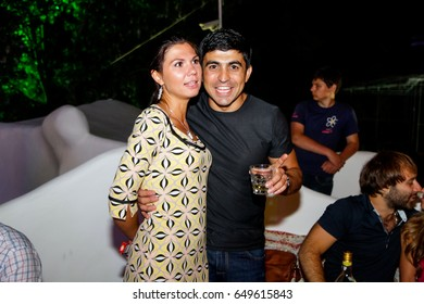 Odessa, Ukraine May 17, 2013: Ibiza night club. People drink alcohol, smiling and posing on cam during concert in night club party. Man and woman have fun at club. Boy and girl at night club