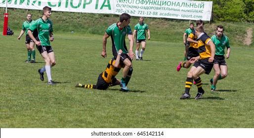 ODESSA, UKRAINE - May 21, 2017: European Rugby Champions Cup POLITECHNIK - Odessa (Striped) and SPORTING - Moldova (Greens) Rugby ball on field. Rugby match hard fight for ball. Rugby players on field
