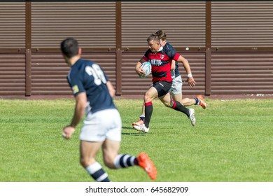 ODESSA, UKRAINE - May 21, 2017: Tough rugby derby of Odessa teams CREDO (red) and ACADEMY OF SPORTS. Rugby ball on field. Rugby is tough fight for the ball. Competitors rugby in field