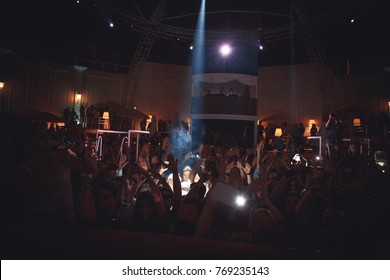 Odessa, Ukraine May 23, 2014: Night club dj party people enjoy of music dancing sound with colorful light, smoke machine, lights show and dance show. Hands up in the earth.