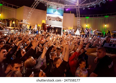 ODESSA, UKRAINE - MAY 24 2014: people having fun in a nightclub at a concert during  creative light and music show. Cheerful young people showered with confetti and a great stage smoke on a club party