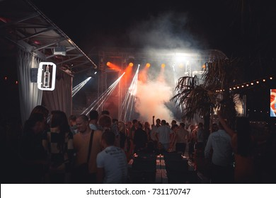 Odessa, Ukraine May 24, 2014: Ibiza night club. Night club dj party people enjoy of music dancing sound with colorful light, smoke machine, lights show. Hands up in the earth.
