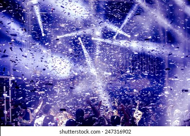 Odessa, Ukraine - May 31, 2014: Large crowd of people having fun in a nightclub at a concert during the creative light and music show. Cheerful young people showered great candy on club party.