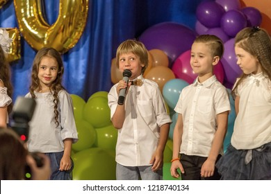 Odessa, Ukraine - May 31,2018: Children's musical group sing and dance on stage during graduation concert of elementary school. Children play. Emotional children's show on stage. Children's creativity