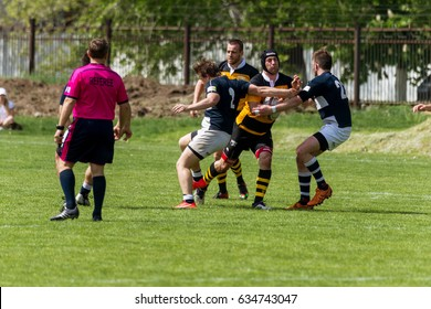 ODESSA, UKRAINE - May 6, 2017: Tough brutal, tough rugby fight between adult teams. Derby Rugby struggle. Players tightly grasp opponents in fight for ball in rugby cup
